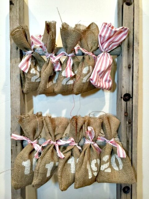 Make this super easy reusable advent calendar with a ladder and some burlap bags! So adorable, the kids will love it!