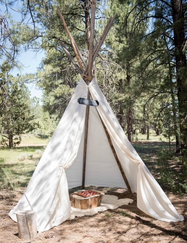 This outdoor woodland wedding set up a teepee for the kids to play in during the reception. Genius!