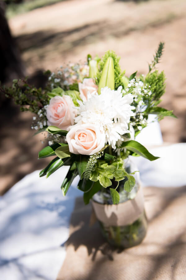 Simple flower arrangements for an outdoor woodland wedding. That blush rose is perfection!