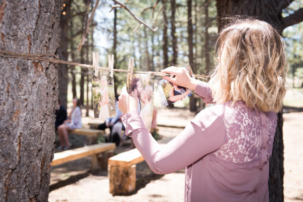Clotheslines with engagement pictures for a special touch at an outdoor woodland themed wedding.