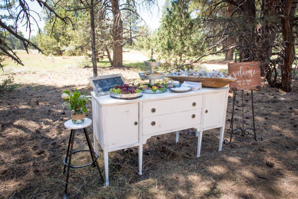A simple white buffet adorned with sweets and treats for guests at an outdoor woodland wedding. So classic.