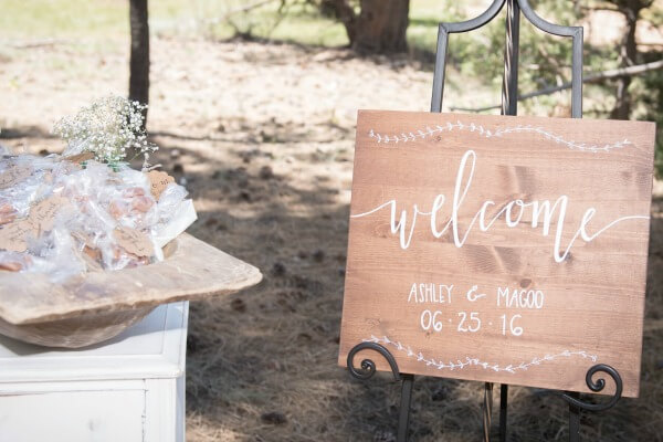 Love this welcome sign for a wedding. The rustic combined with the white is perfect!