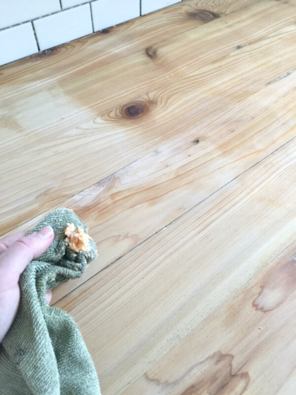Sealing butcher block countertop with wax.