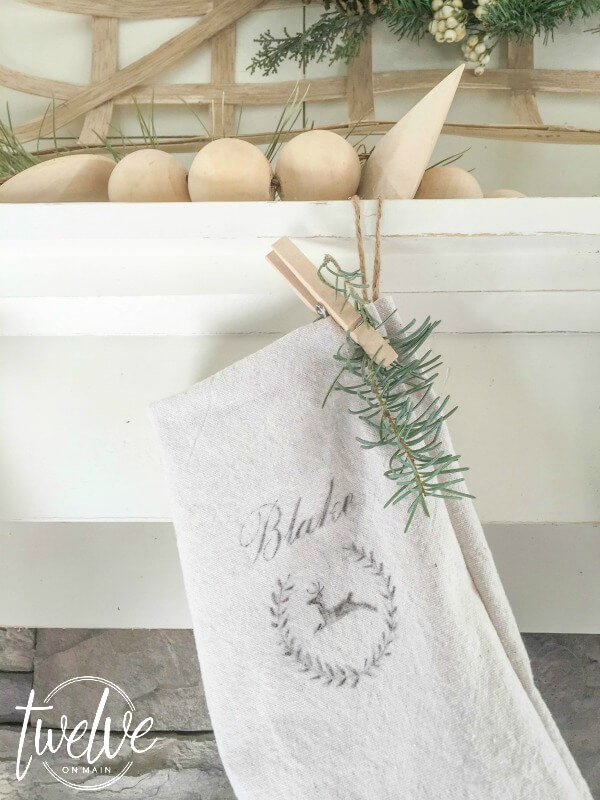 I love this farmhouse style Christmas mantel That driftwood reindeer is so perfect and those drop cloth stockings are amazing!