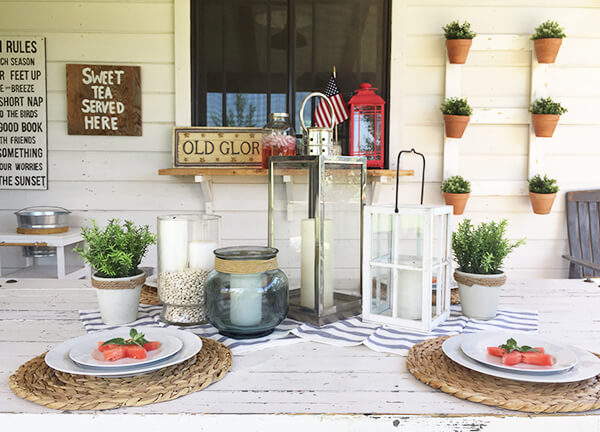 Farmhouse style patriotic outdoor tablescape for the 4th of July. Striped fabric, watermelon, seagrass placemats, and red, white and blue, all on a chippy farmhouse table.