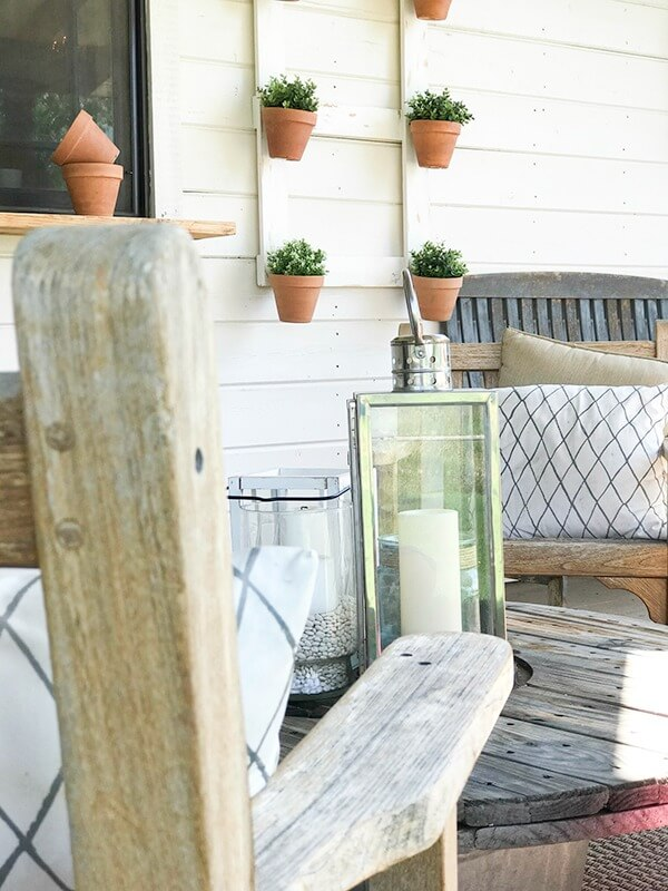 Salvaged furniture, farmhouse wall planters, and unique lanterns create a lovely farmhouse summer porch!