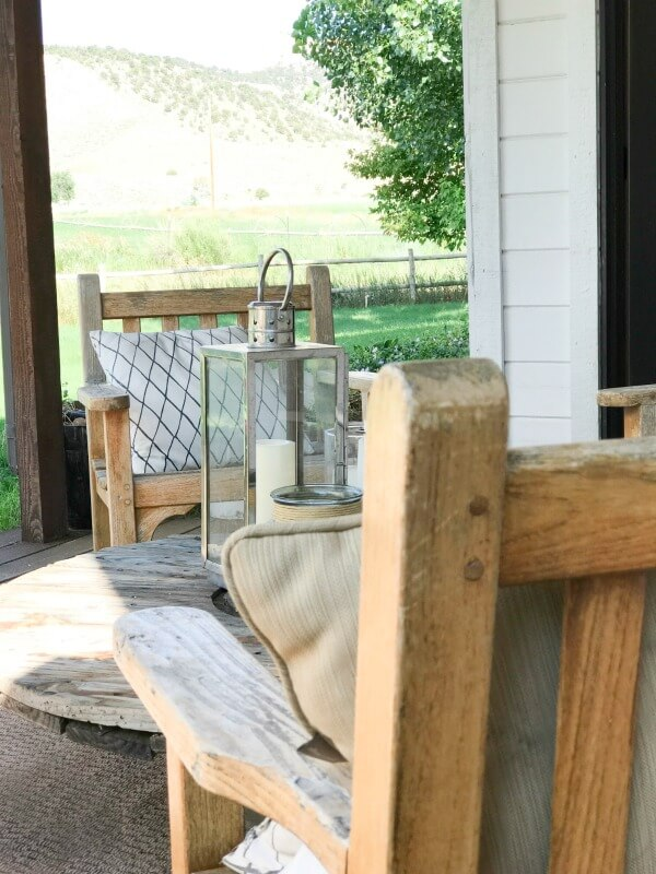 Lovely farmhouse summer porch decor! Love those lanterns and those teak chairs!
