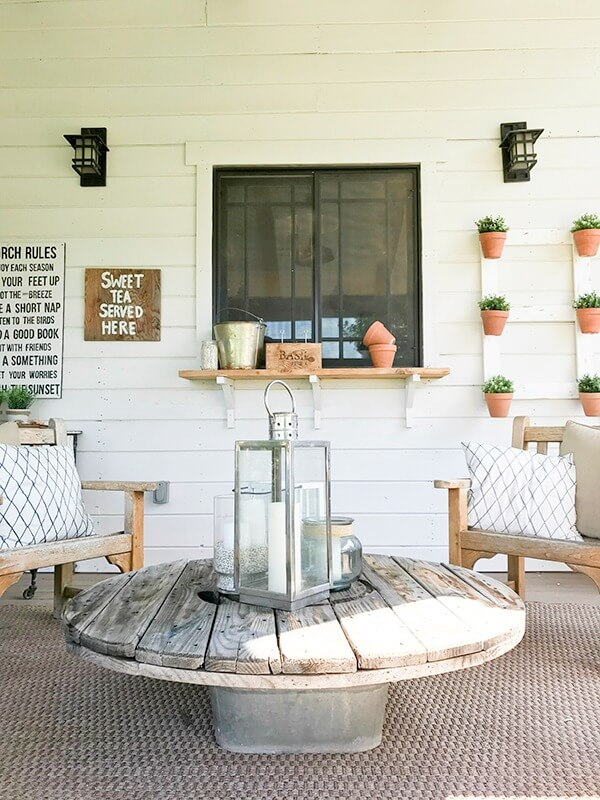 I love this easy salvaged coffee table! Its made from a wire spool and galvanized tub! Goes so well with the farmhouse summer porch decor!