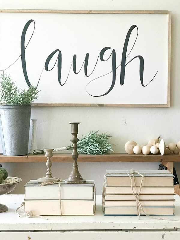 Farmhouse living room ideas complete with large farmhouse signs, pottery, rustic wood, and fresh lilac cuttings. A touch of navy blue accents finishes off the space.