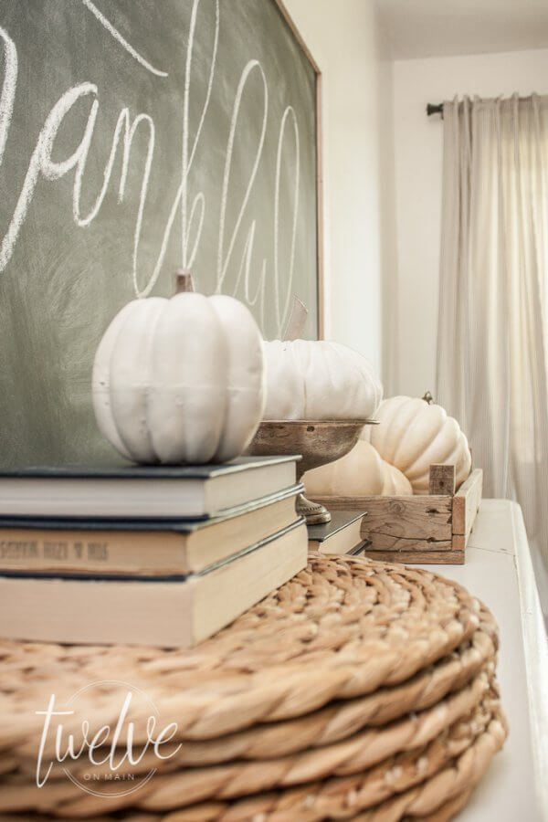Simple farmhouse fall dining room features....ticking stripe fabric, white pumpkins, old books, and chalkboard art.