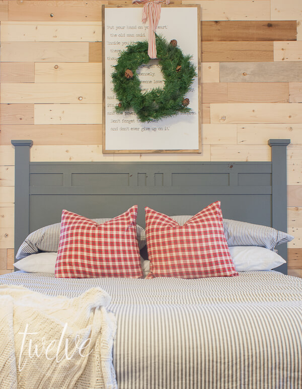 Boys bedroom decorate for Christmas with a wreath, holiday pillows, and twinkle lights.