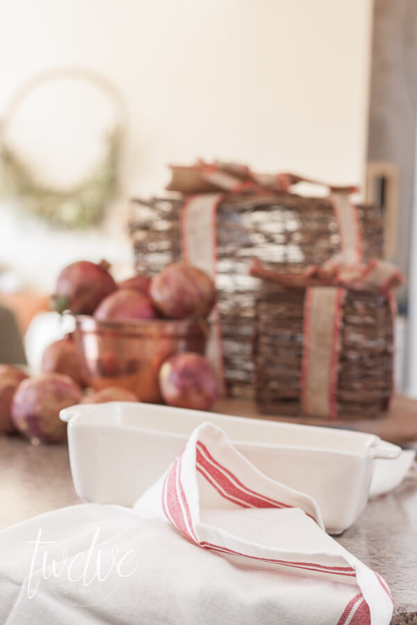 Faux gifts, pomegranates, and red grainsack towels for this farmhouse Christmas kitchen.