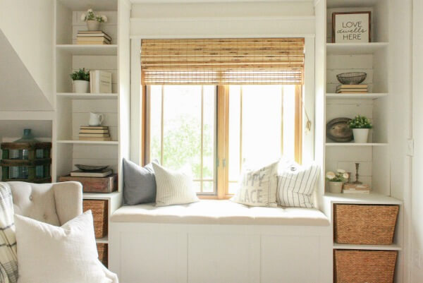 Get cozy in this farmhouse style window seat with a cozy board and batten wall treatment and gorgeous farmhouse decor