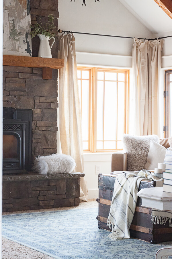 This cozy family room looks amazing with dropcloth curtains, a stacked stone fireplace, blue vintage area rug, and an antique steamers trunk. Beautiful.