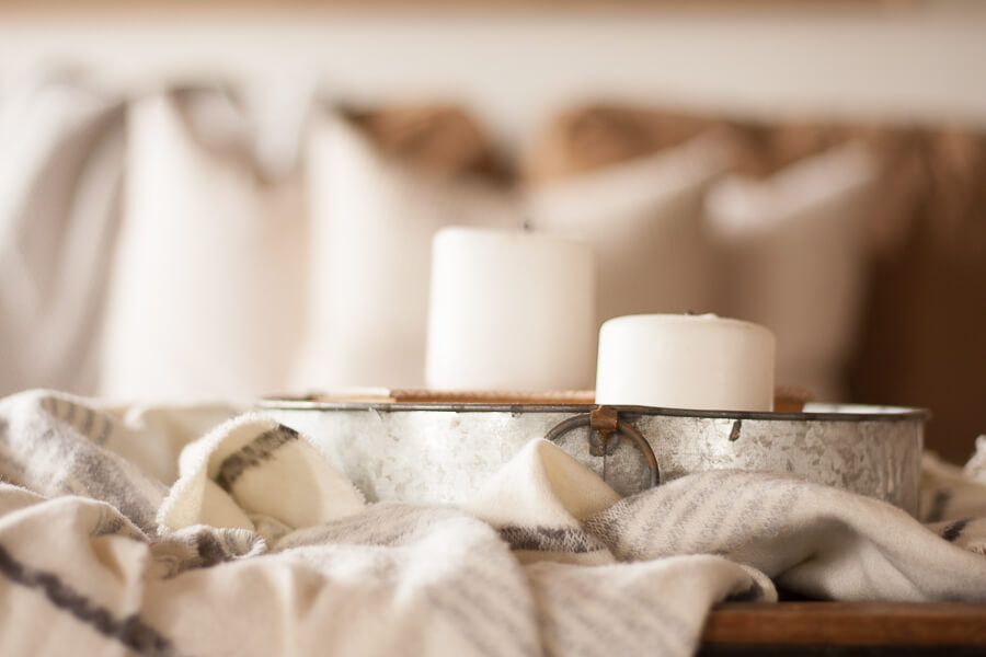 I love combining different textures when decoratiing my farmhouse living room. Love the look of a cozy throw blanket, a galvanized tray, and some simple white candles.