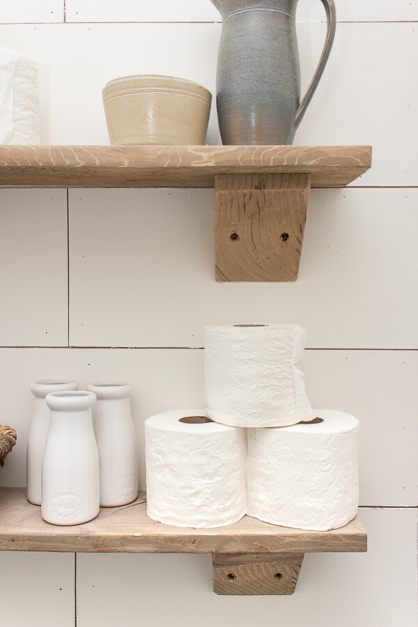 Use rustic wood shelves to store toilet paper in the bathroom. Great organization and stylish looks!
