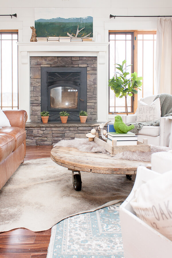 Cozy farmhouse living room with drop cloth curtains, farmhouse artwork, hardwood floors, and a stacked stone fireplace.