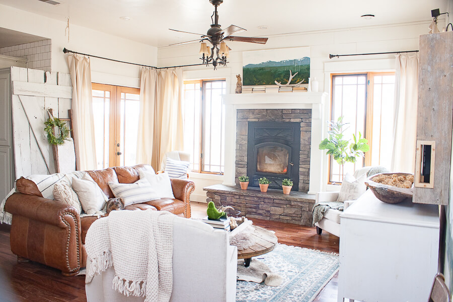 Calming farmhouse living room with canvas drop cloth curtains, farmhouse style artwork, and textured rugs and throws. Beautiful!
