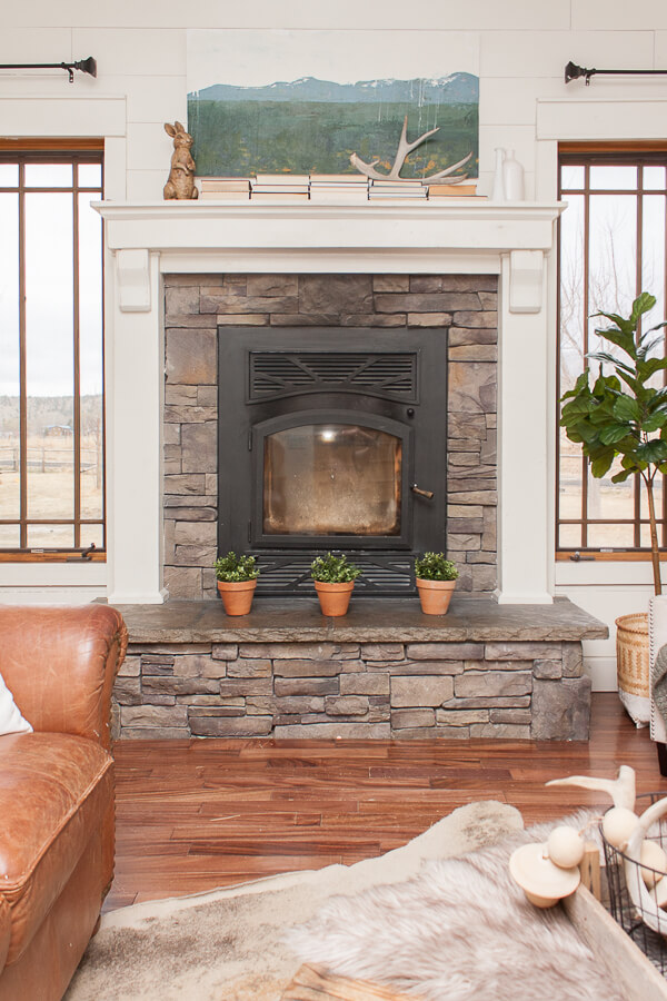 Farmhouse spring decor on this stacked stone fireplace and mantel. Gorgeous custom artwork!