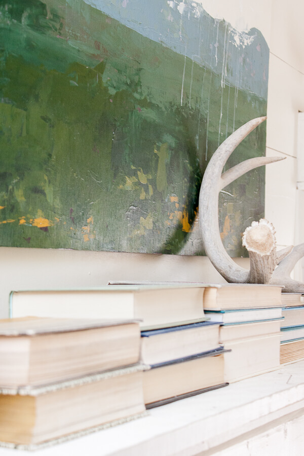 Farmhouse style spring decor with books, custom artwork and deer antlers