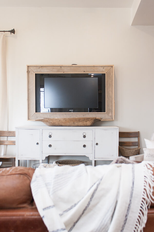 Want to hide that ugly television?  Make your own TV frame with this simple DIY tutorial and create a stylish look for your home.