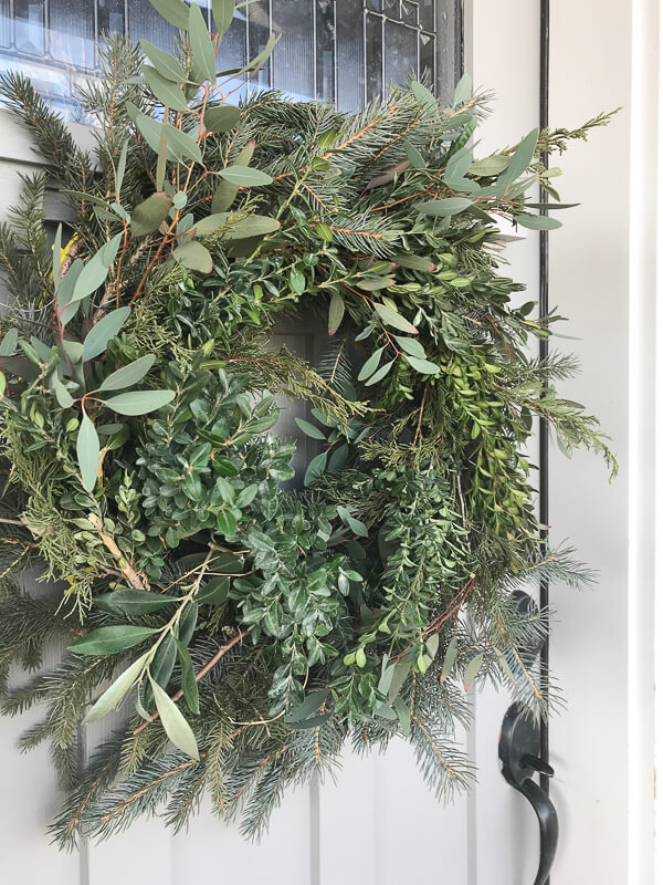 Woodland style fresh Christmas wreath made with pine bough cuttings, olive branches, eucalyptus, and boxwood!