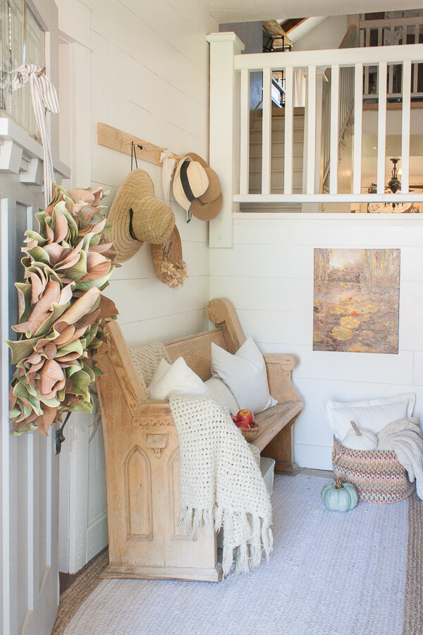 Farmhouse fall decor in the entry. Entryway fall decor, with neutral layers of texture and pops of color.