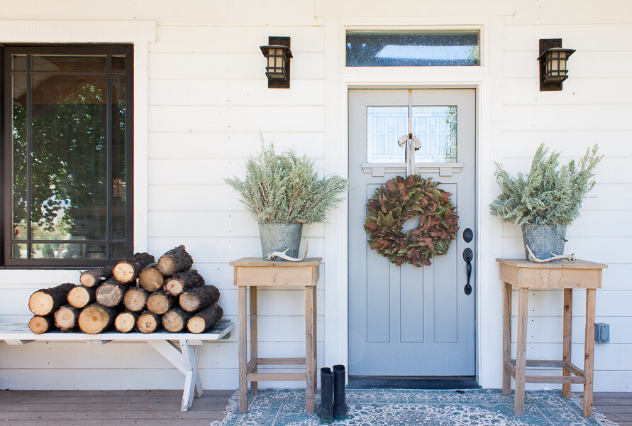 Farmhouse fall decor eith firewood, zinc buckets, and large rug, and magnolia wreath!