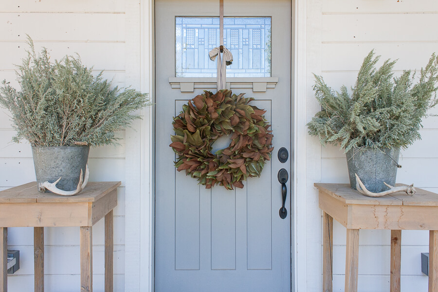 Fall decor on the porch with a magnolia wreath and zinc buckets with sagebrush