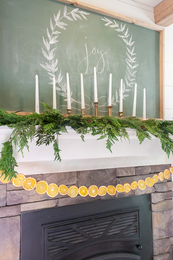 Scandinavian Christmas mantel with dried orange garland, fresh greenery, and amazing vintage Baldwin brass candlesticks!
