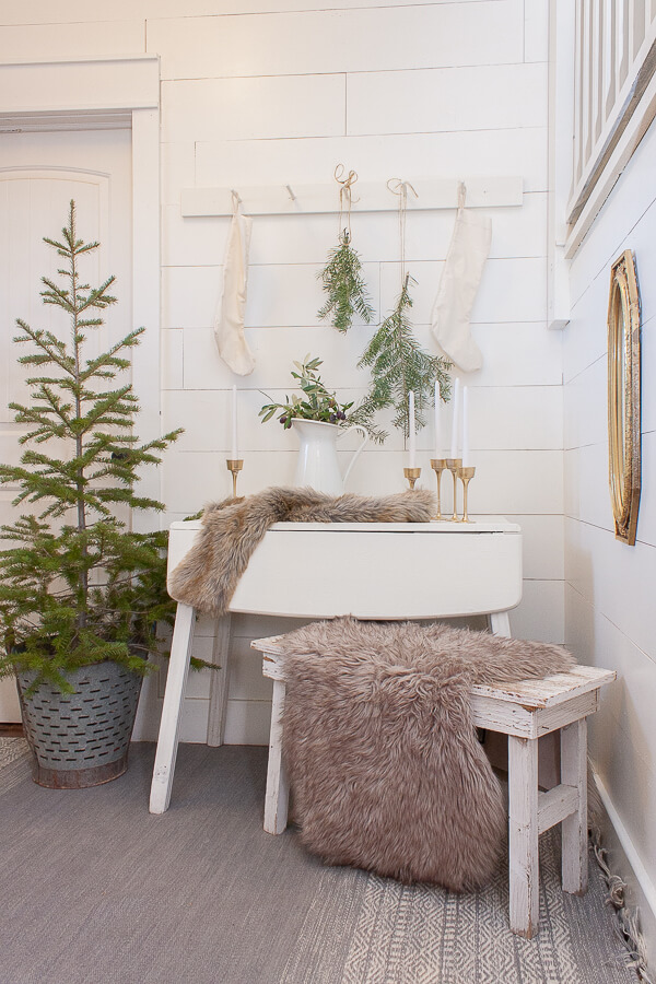 White walls, white furniture, fresh cut Christmas tree, Scandinavian Christmas elements including furs, fresh natural elements, and a touch of metal.