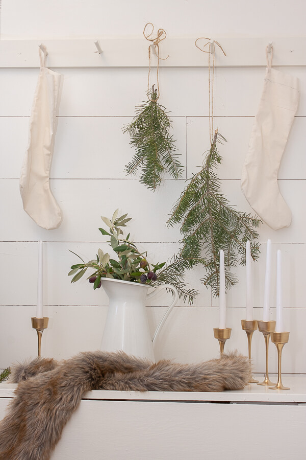 Scandinavian Christmas entryway decor including furs, brass candlesticks, handmade stockings, and tree clippings.