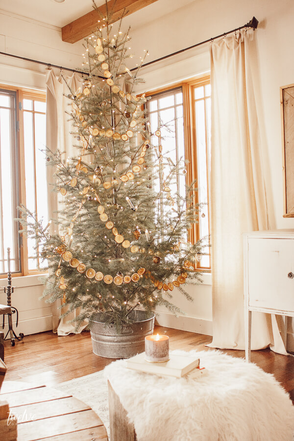 Scandinavian style Christmas tree with dried orange garland, copper twinkle lights, and some simple metallic ornaments.