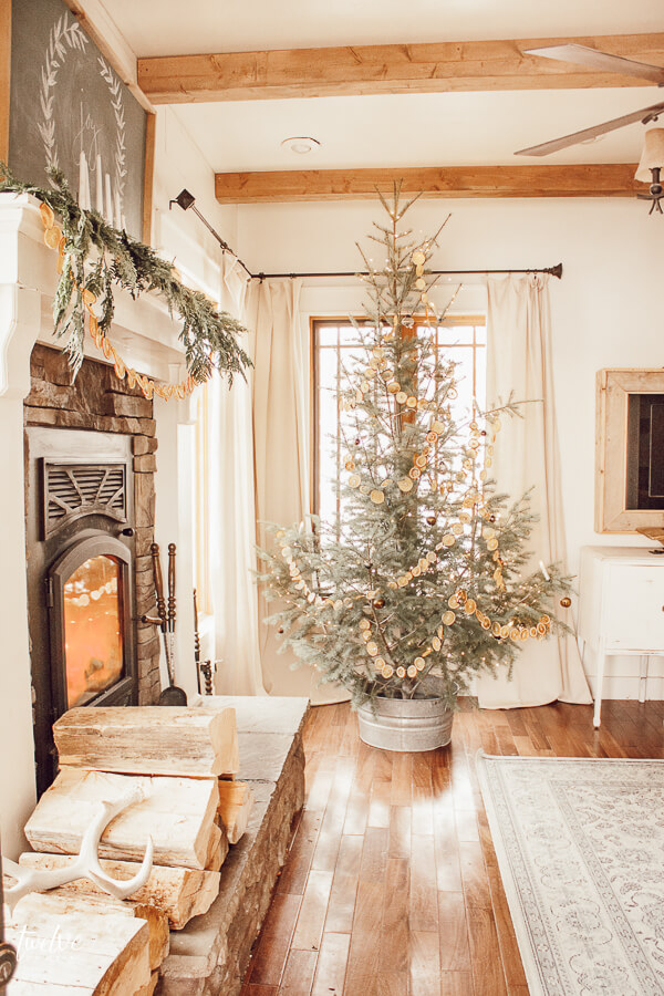 Scandinavian Christmas tree, dried orange garland, use of sheepskin, white decor accents, lots of wood, and those wood beams!