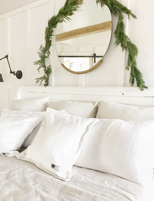 Simple and elegant Scandinavian farmhouse style Christmas bedroom decor. White linens, antique gold mirror, faux cedar garland, and tons of white pillows!