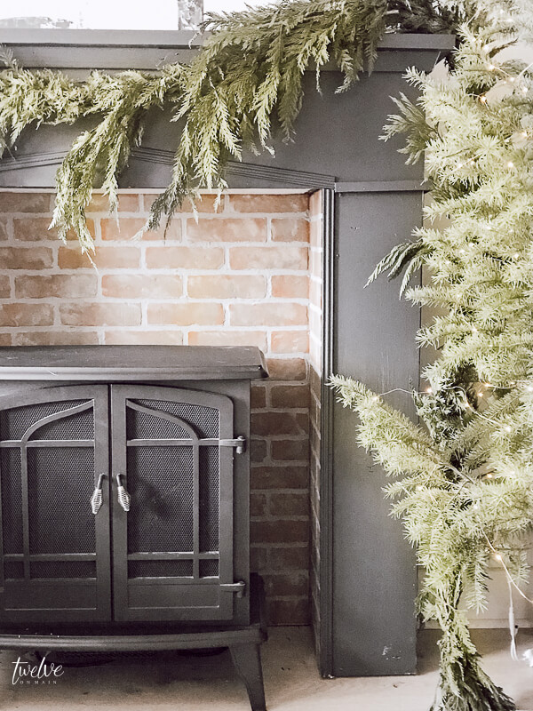 I love everything about this shot! Mantel painted with Farrow and Ball Downpipe, brick insert is amazing and the real evergreen garland is amazing!