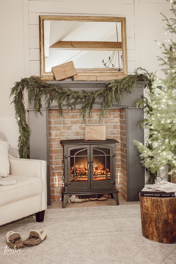 Farmhouse style Christmas bedroom decor, with a beautiful faux brick fireplace, mantel painted in Farrow and Ball Downpipe, real cedar garland, a golden mirror, and so much more.  Such a cozy space full of elegant and effortless Christmas decor!
