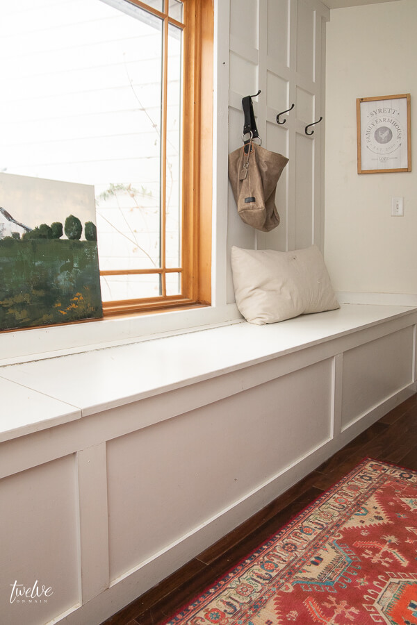 Farmhouse style white mudroom complete with gorgeous custom artwork and colorful vintage rug.