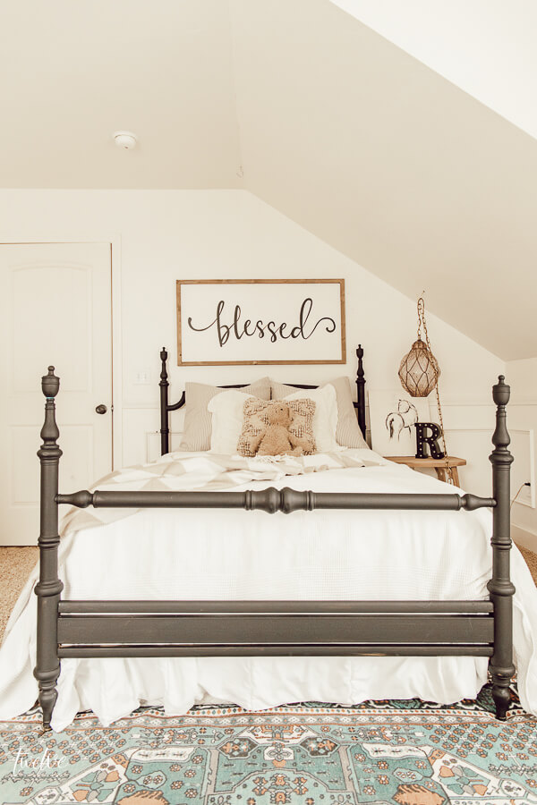 A little girls bedroom dream! Love the black bed, layered textures, a pop of color on the rug and the vintage glass light hanging above the nightstand!