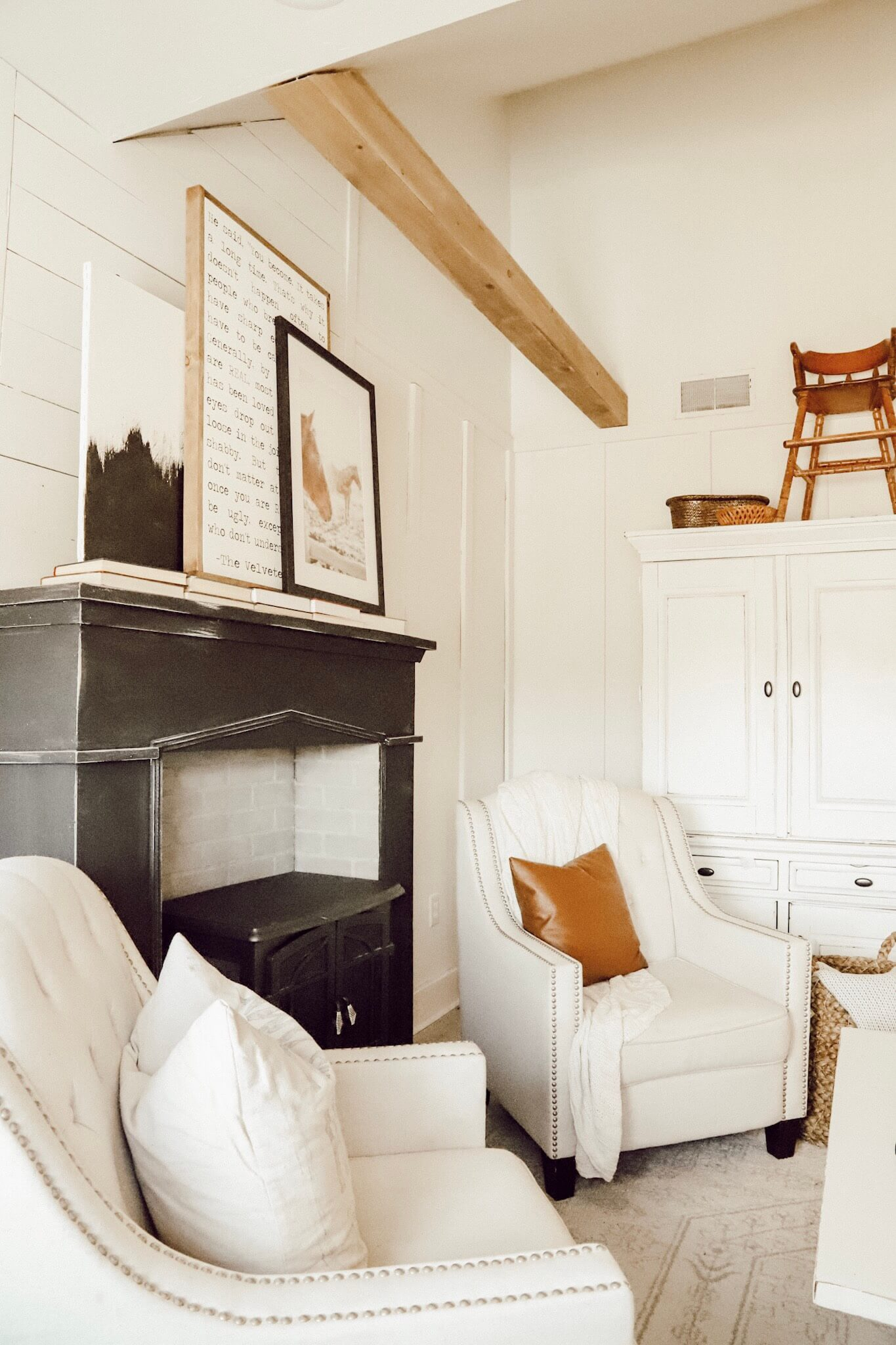 This space is amazing!  Love the white along the striking painted fireplace in black, the wood beams and the horse art!