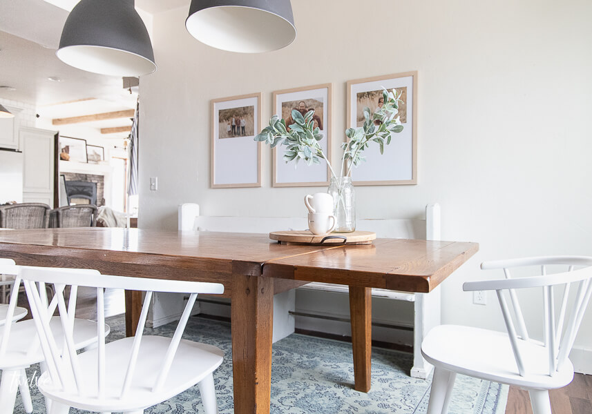 Custom framed art, IKEA Hektar lights, an incredible Mohawk rug, and the most incredible white spindle chairs  round out this modern farmhouse dining room design!