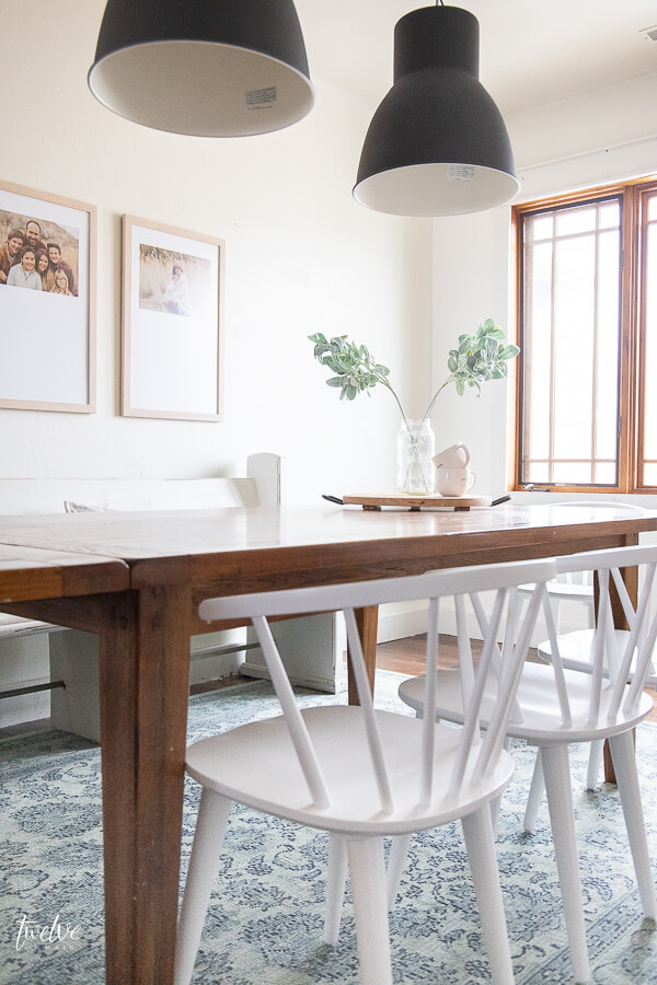 A modern farmhouse dining room design complete with white spindle chairs, a vintage church pew, custom framed artwork, and IKEA Hektar lights!
