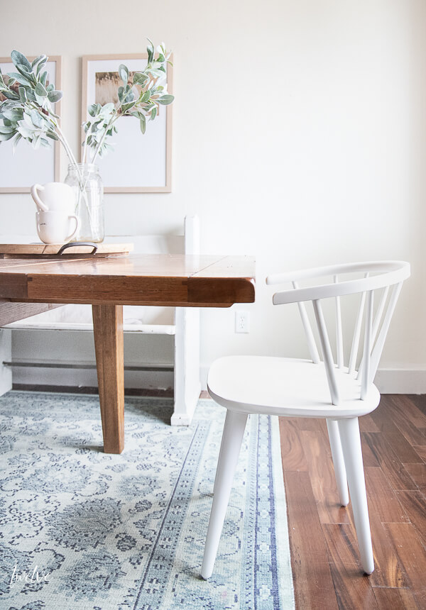 Amazing simple white spindle dining chairs are perfect with this rustic farmhouse table.