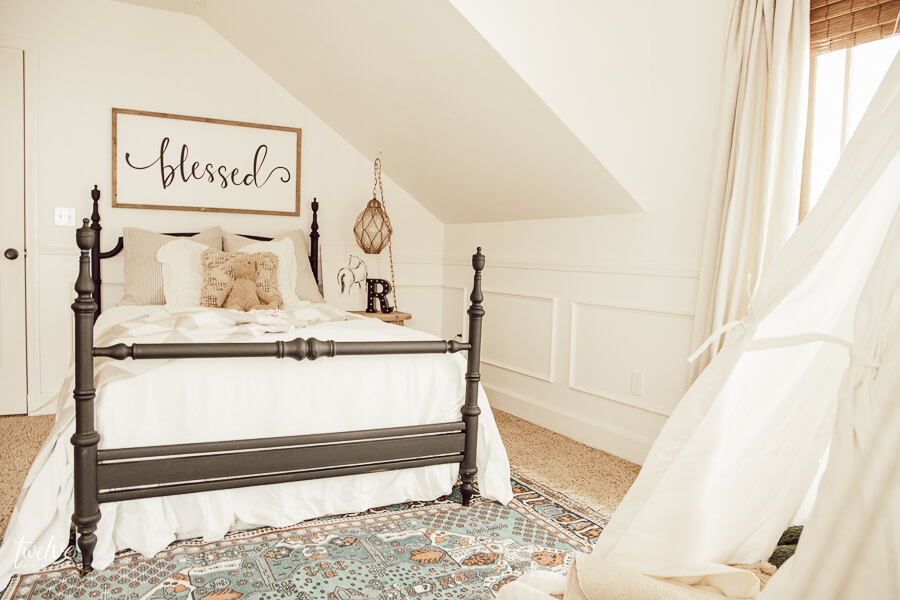Boho farmhouse inspired little girls bedroom with white bedding, a black metal bed, a canvas teepee and a hanging chair!