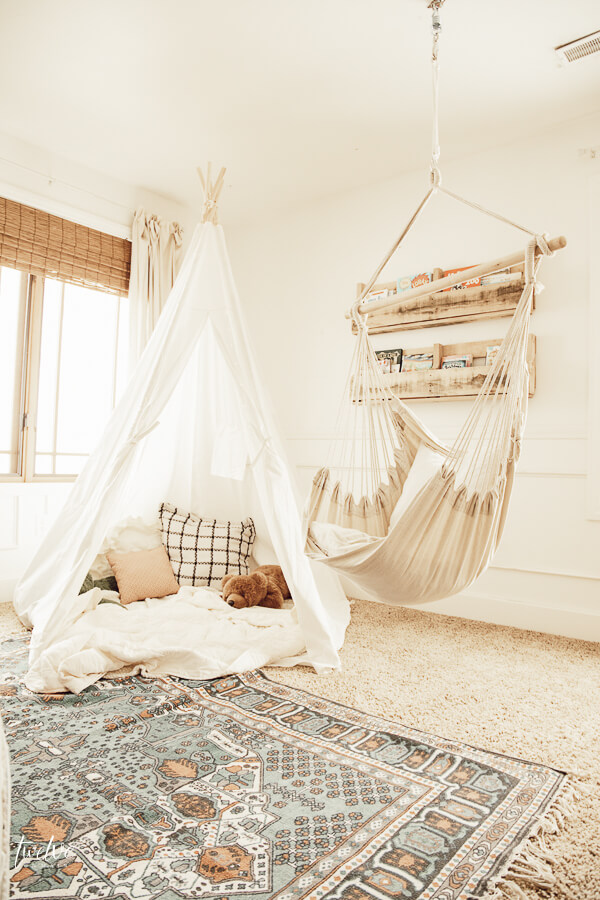 Boho style reading nook with a teepee and a hanging chair!