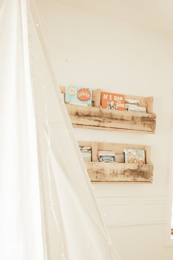 Pallet bookshelves hold our daughters books in her cozy boho style reading nook.