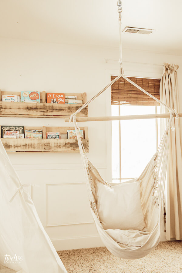 Cozy boho style girls reading nook, complete with a teepee and a hanging chair!