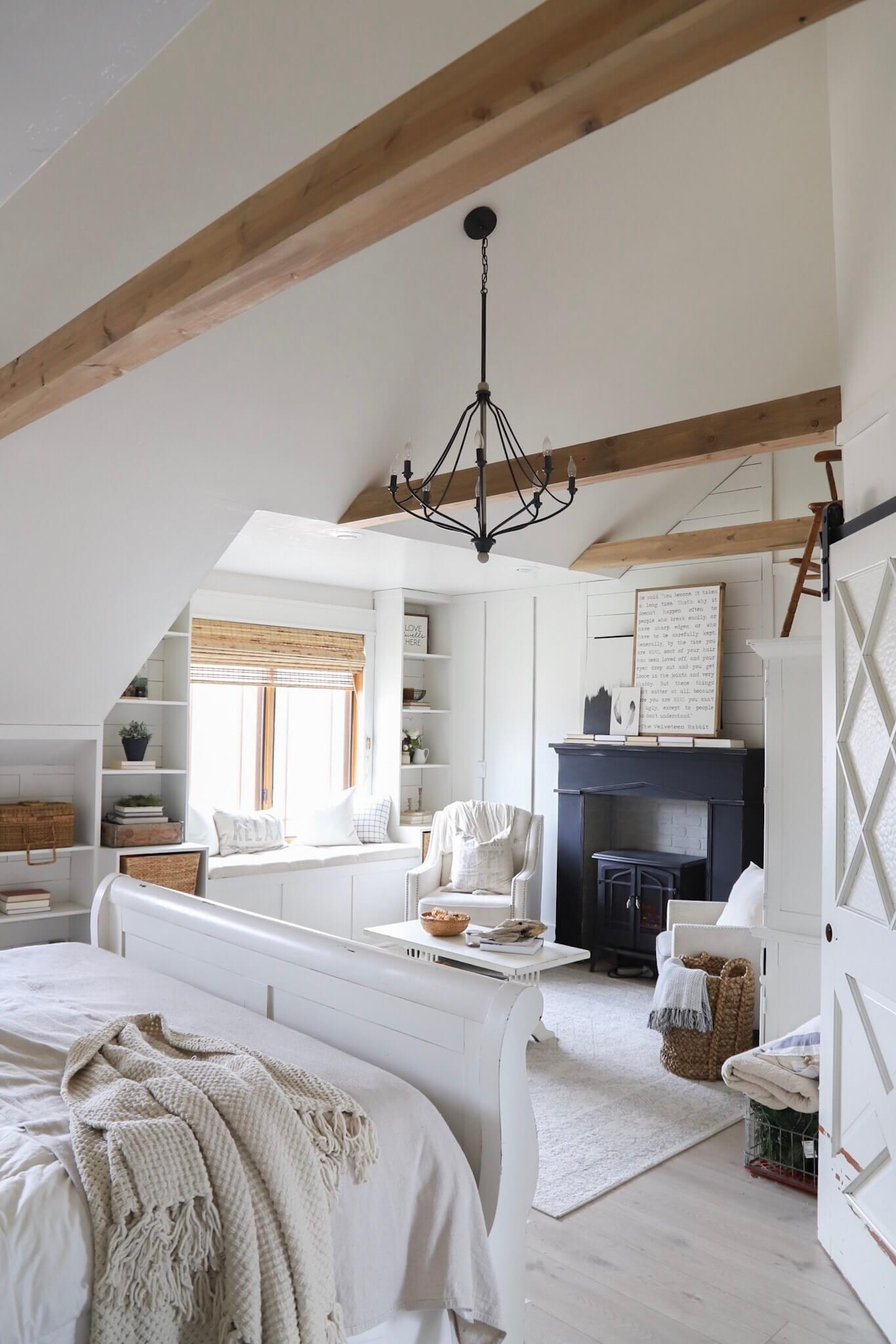 Gorgeous master bedroom retreat with exposed beams, a farmhouse style fireplace and so much more!