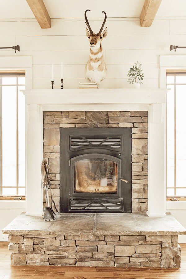 Beautiful fireplace with an Antelope mount, mini olive tree, and a few black candlesticks.