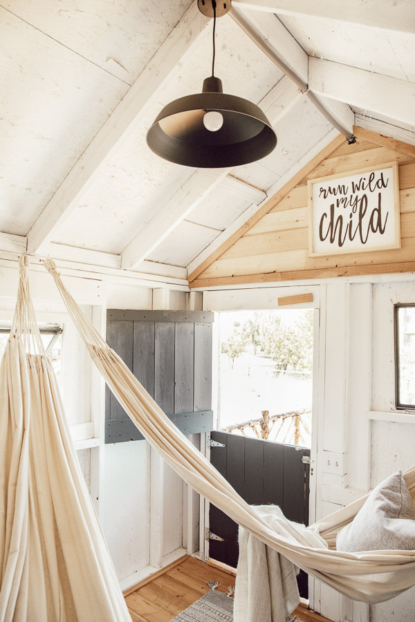 Check out this amazing farmhouse style treehouse design! Gorgeous details, hammocks, a front porch, lights and more!